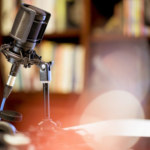microphone-in-studio-surrounded-by-equipment-under-the-lights-with-blurry-background-scaled.jpg